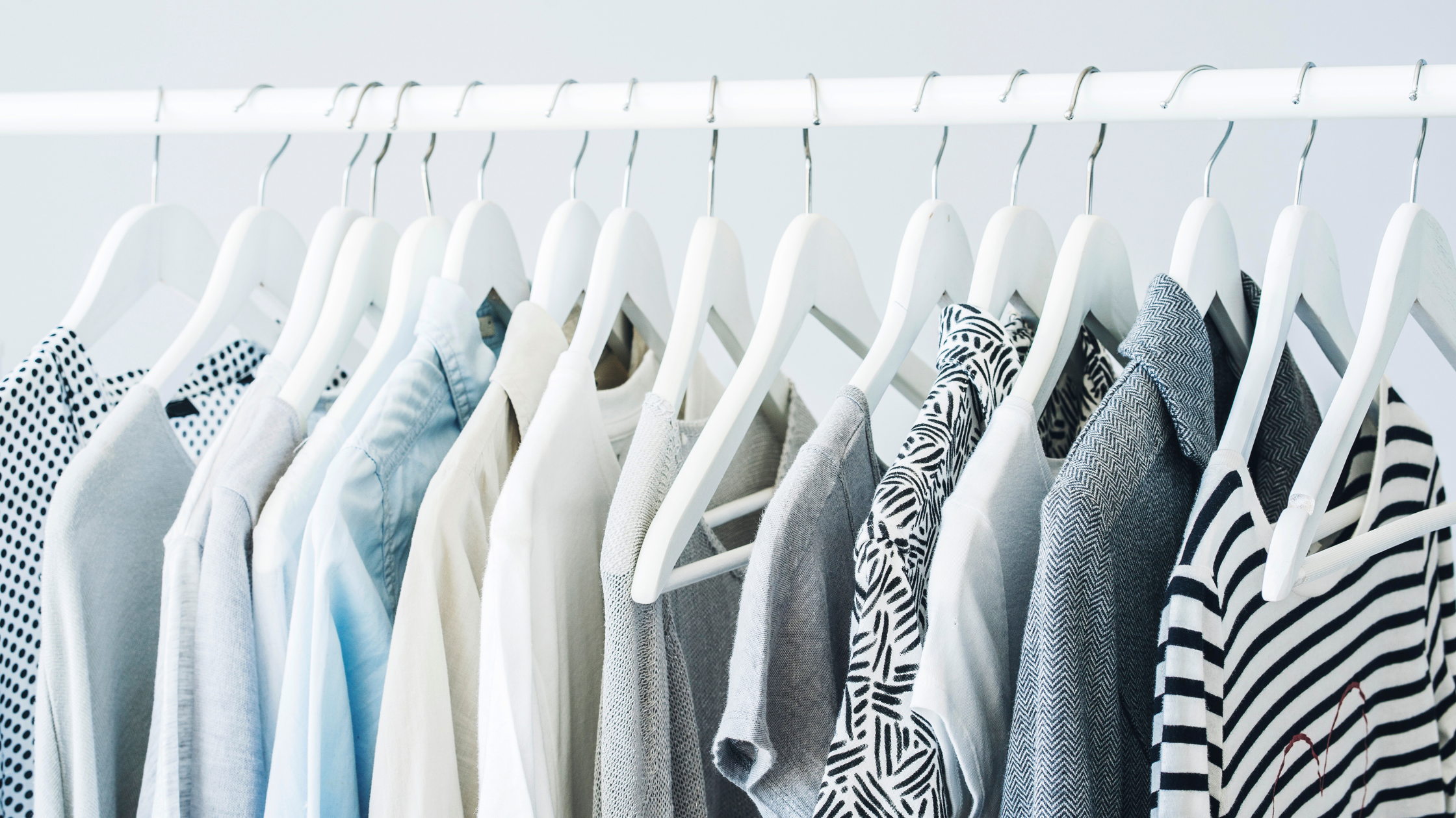 Women's tops hanging in closet - Tips To Declutter Your Clothes